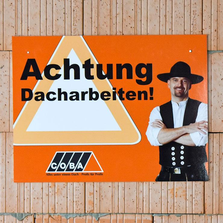 Kombination Werbe- und Warnschild für Dachdeckerarbeiten.