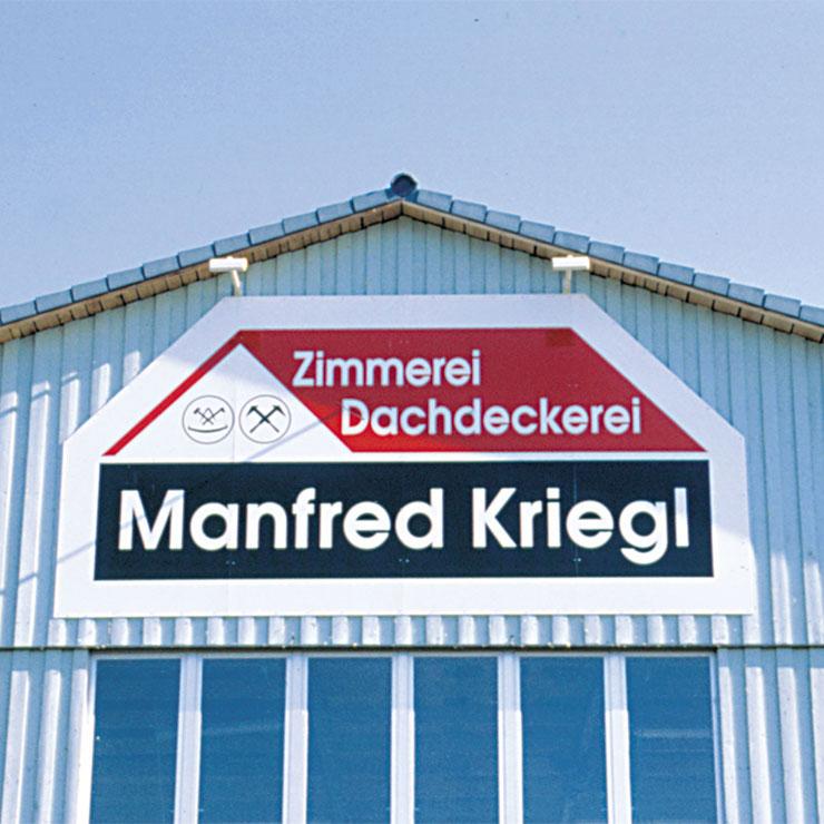Formgeschnittene Schildertafel für Fassadenwerbung an einer Produktionshalle.