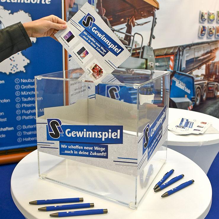 Losbox aus Acrylglas mit Gewinnspielkarten.